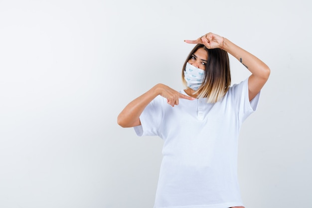 Jeune fille pointant à droite et à gauche avec l'index en t-shirt blanc et masque et à la vue de face, confiant.