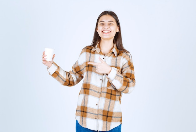 Jeune fille pointant sur une tasse de thé sur un mur blanc.