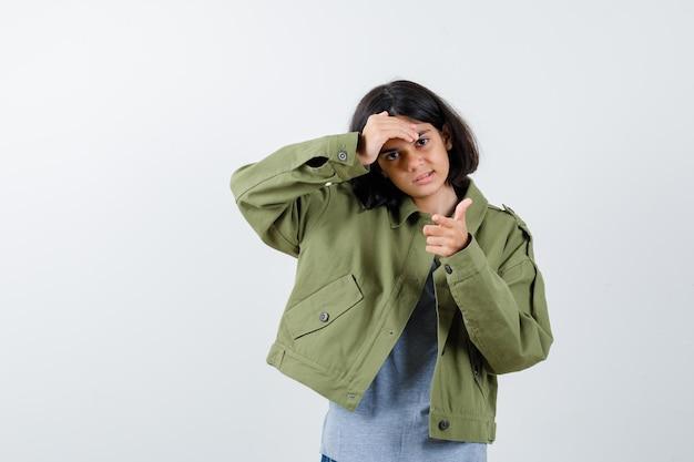 Jeune fille pointant tout en tenant la main sur le front en pull gris, veste kaki, pantalon en jean et l'air sérieux. vue de face.