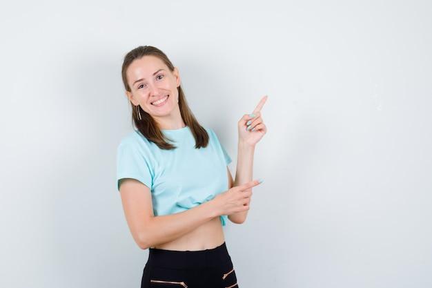 Jeune fille pointant vers le haut, debout sur le côté en t-shirt turquoise, pantalon et l'air heureux.