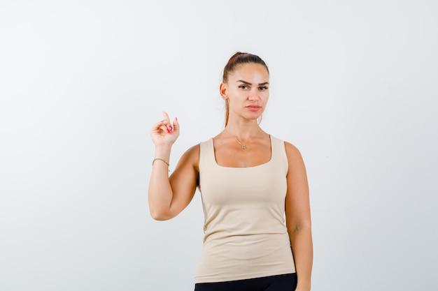 Jeune fille pointant vers le haut avec l'index en haut beige, pantalon noir et à la grave, vue de face.