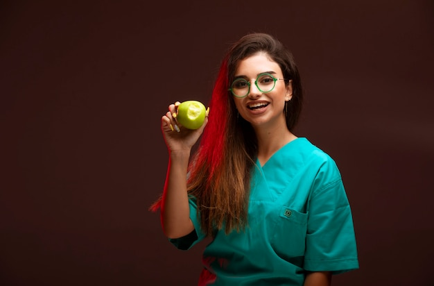 Jeune fille avec une pomme verte dans la main.