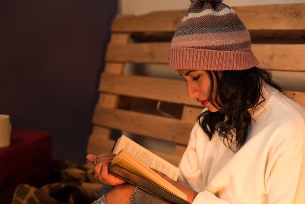 Jeune fille portant un chapeau d'hiver en lisant un livre concentré