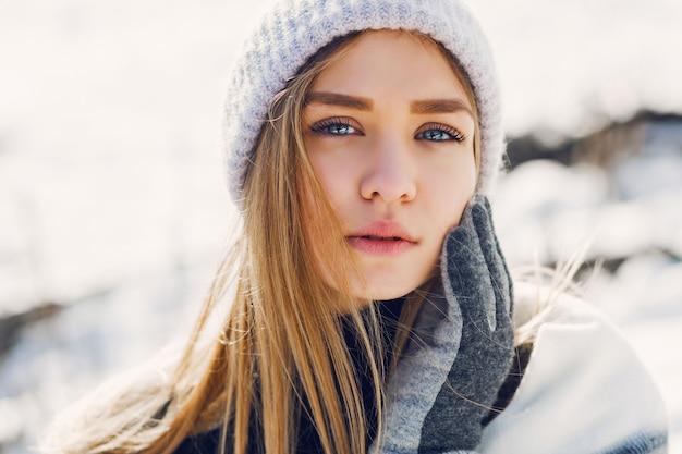 Jeune fille portant une couverture sur un champ enneigé