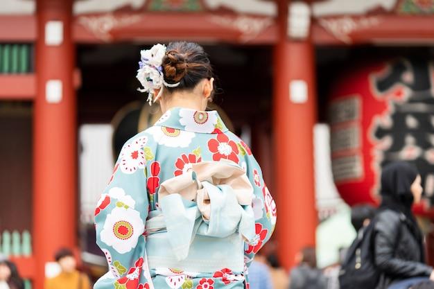 Jeune fille portant un kimono japonais se tenant devant le temple sensoji à tokyo,