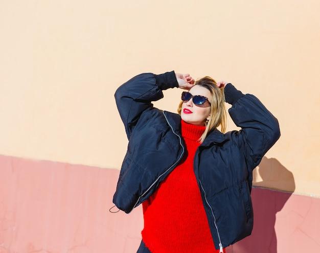 Une jeune fille portant des lunettes de soleil, une veste noire et un pull rouge pose contre un mur. lumière forte