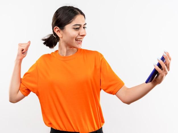 Jeune fille portant un t-shirt orange tenant le poing serrant le smartphone heureux et excité debout sur un mur blanc