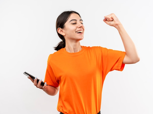 Jeune fille portant un t-shirt orange tenant le poing serrant le smartphone heureux et excité souriant joyeusement se réjouissant de son succès debout sur un mur blanc