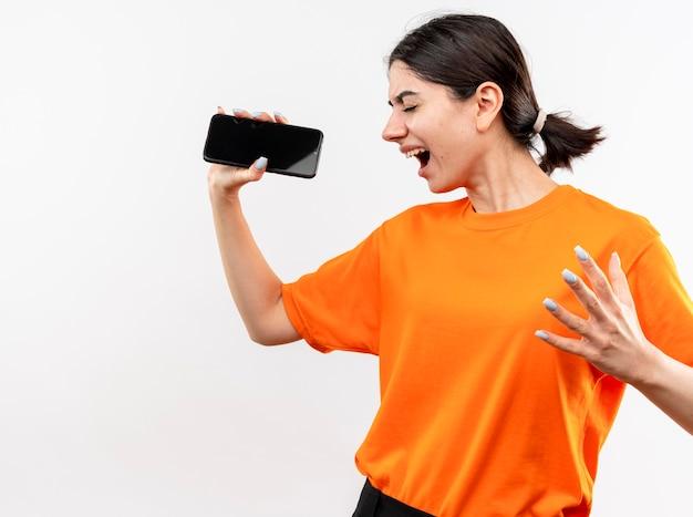 Jeune fille portant un t-shirt orange tenant un smartphone criant fou heureux debout sur un mur blanc