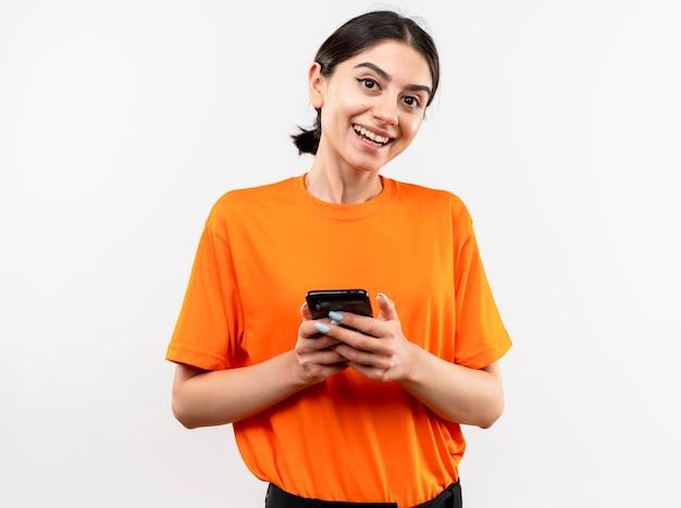 Jeune fille portant un t-shirt orange tenant un smartphone souriant avec un visage heureux debout sur un mur blanc