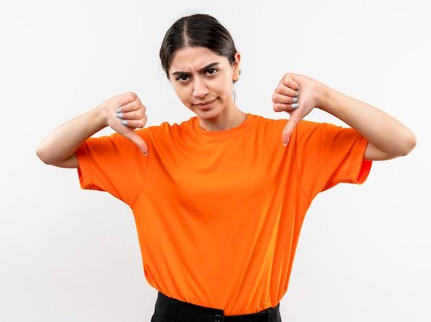 Jeune fille portant un t-shirt orange avec visage sérieux fronçant les sourcils montrant les pouces vers le bas debout sur un mur blanc