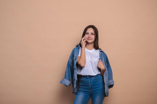 Jeune fille portant des vêtements en jean à l'aide de téléphone sur mur beige