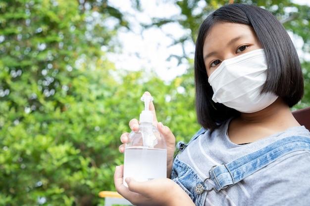 La jeune fille porte un masque de protection et a des maux de tête et une quarantaine pour surveiller l'infection par le virus dans le jardin à la maison. concept de distance sociale.