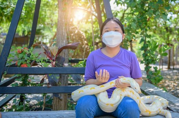 Une jeune fille porte un masque et tient un python albinos, concept d'animal de compagnie