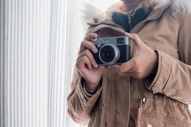 Jeune fille porte un pardessus avec un appareil photo rétro sur un rideau brillant