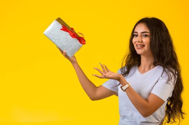 Jeune fille posant avec une boîte-cadeau dans la main et souriant.
