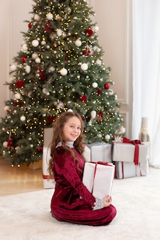 Jeune fille posant avec des cadeaux de noël