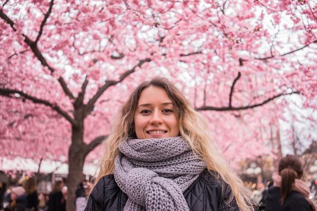 Jeune fille posant sur le fond des arbres roses en fleurs. printemps. sakura.