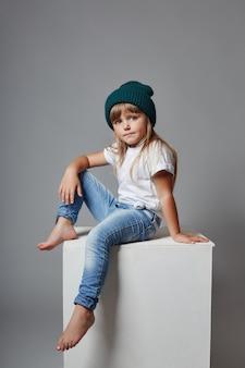 Jeune fille posant sur un fond gris, émotions gaies lumineuses sur le visage de la fille