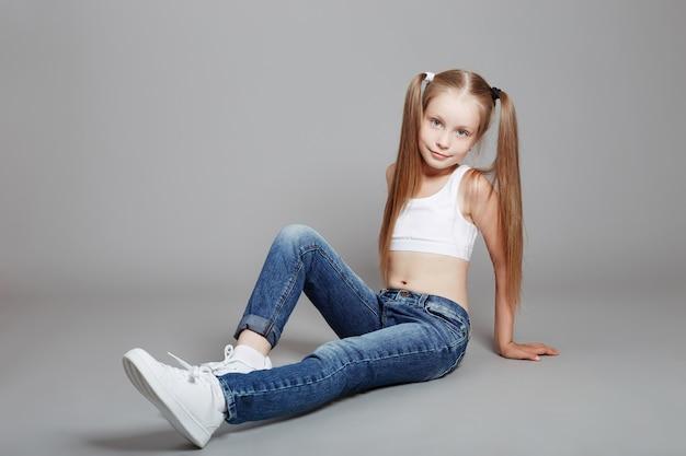 Jeune fille posant sur un fond gris