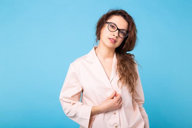 Jeune fille posant en pyjama sur mur bleu