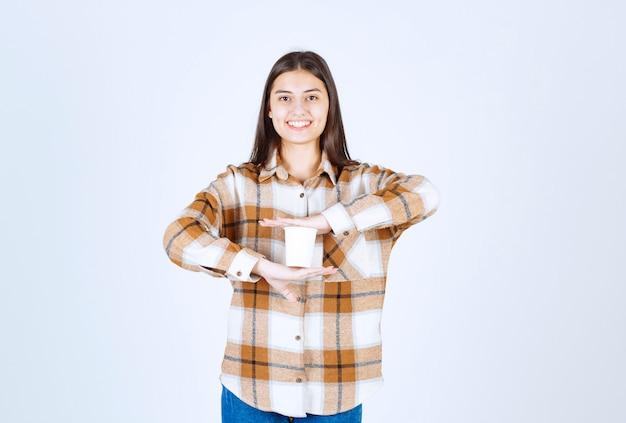 Jeune fille posant avec une tasse de thé sur un mur blanc.