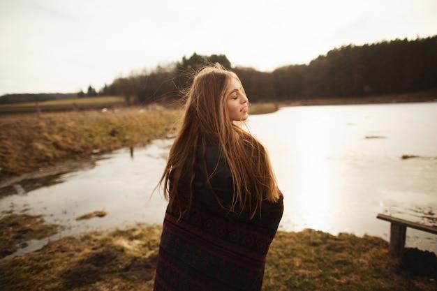 Une jeune fille pose au bord d'un lac