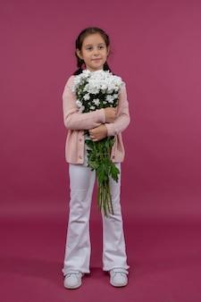 Une jeune fille pose sur un fond rose avec des fleurs dans ses mains chrysanthème