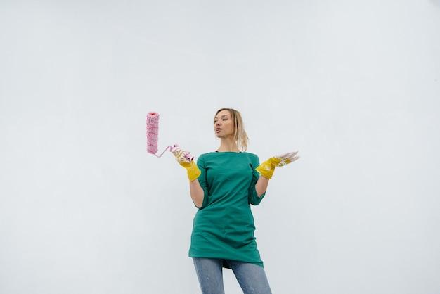 Une jeune fille pose avec un rouleau devant un mur blanc. réparation de l'intérieur.