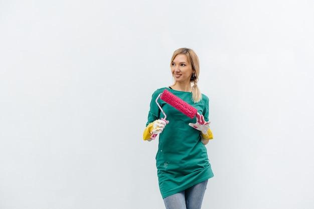 Une jeune fille pose avec un rouleau rose avant de peindre un mur blanc. réparation de l'intérieur.