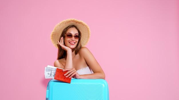 Jeune fille positive au chapeau de paille et lunettes de soleil avec billets et valise fond studio rose smi...