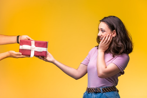 Jeune fille prenant une boîte-cadeau de son amie et est surprise