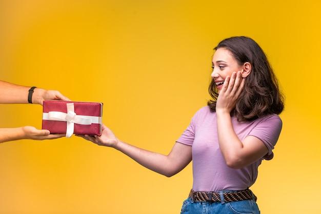 Jeune fille prenant un coffret cadeau de son amie et surprise.