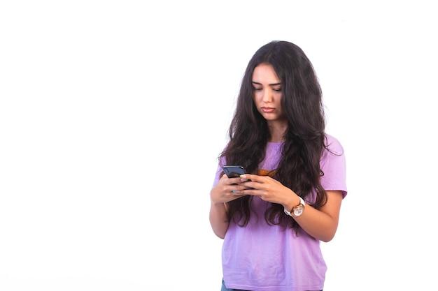 Jeune fille prenant selfie ou faisant un appel vidéo sur fond blanc et a l'air réfléchie.