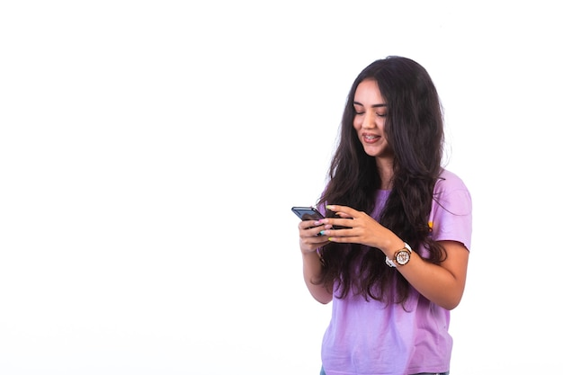 Jeune fille prenant selfie ou faisant un appel vidéo sur un mur blanc.