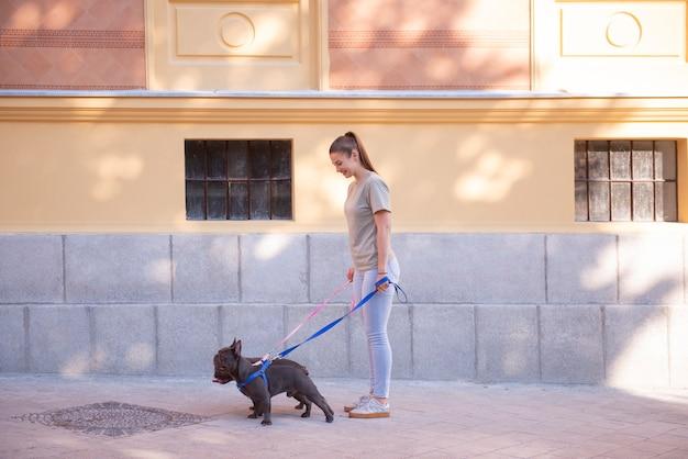 Jeune fille prenant ses mignons bulldogs friech bleu pour une promenade dans les rues