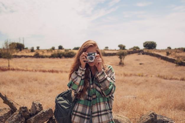 Une jeune fille prend une photo avec un appareil photo analogique