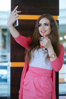Jeune fille de prendre une photo d'elle-même boire un soda