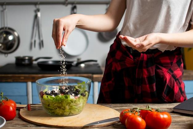 Jeune fille prépare une salade végétarienne dans la cuisine