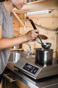 Une jeune fille prépare une soupe sur une cuisinière électrique