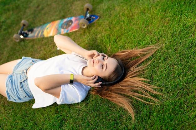 Jeune fille profiter de jeter dans la pelouse verte et écouter de la musique après avoir roulé sur son journal