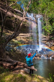 La jeune fille en pull bleu en tournée sur la cascade de yung thong, belle cascade de la province d'oudonthani, en thaïlande.