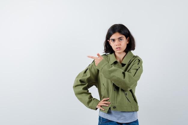 Jeune fille en pull gris, veste kaki, pantalon en jean pointant vers la gauche et tenant la main sur la taille et l'air sérieux, vue de face.