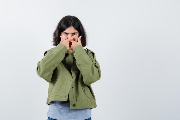 Jeune fille en pull gris, veste kaki, pantalon en jean tenant les deux bras croisés, ne faisant aucun signe et l'air sérieux, vue de face.
