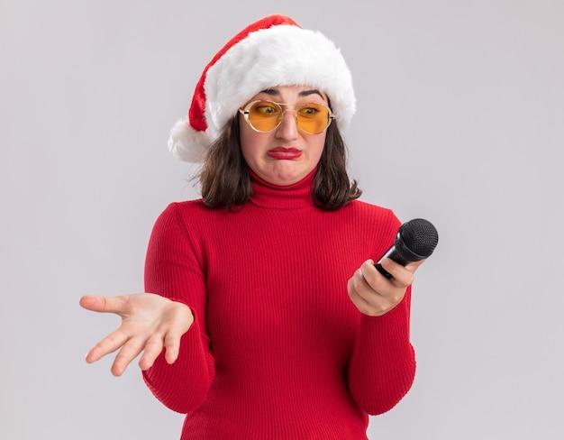 Jeune fille en pull rouge et bonnet de noel portant des lunettes tenant le microphone en le regardant avec une expression confuse avec bras debout sur fond blanc
