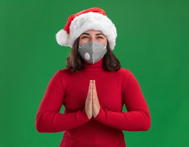 Jeune fille en pull rouge et bonnet de noel portant un masque de protection du visage avec un visage heureux se tenant la main comme un geste namaste debout sur un mur vert