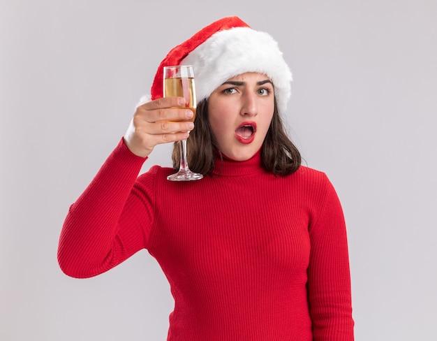 Jeune fille en pull rouge et bonnet de noel tenant un verre de champagne surpris debout sur un mur blanc