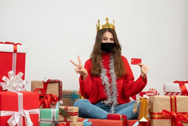 Jeune fille avec pull rouge faisant signe de la victoire assis autour de cadeaux avec masque noir sur blanc