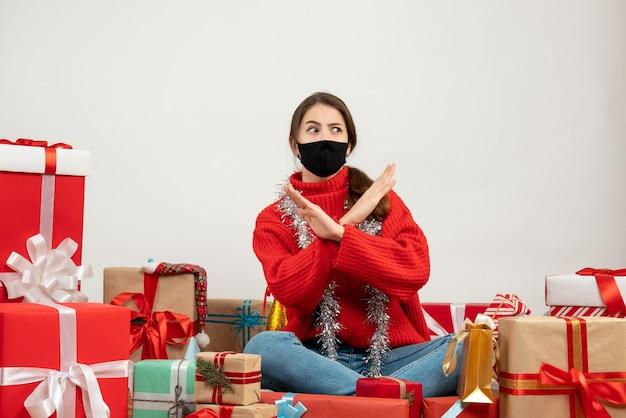 Jeune fille avec pull rouge et masque noir croisant les mains assis autour de cadeaux sur blanc
