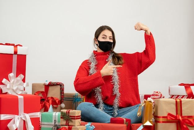Jeune fille avec pull rouge et masque noir exhibant son muscle assis autour de cadeaux sur blanc